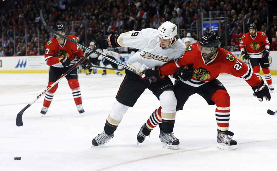 Photo - Chicago Blackhawks defenseman Johnny Oduya (27), of Sweden, pressures Anaheim Ducks left wing Matt Beleskey during the first period of an NHL hockey game, Tuesday, Feb. 12, 2013, in Chicago. (AP Photo/Charlie Arbogast)