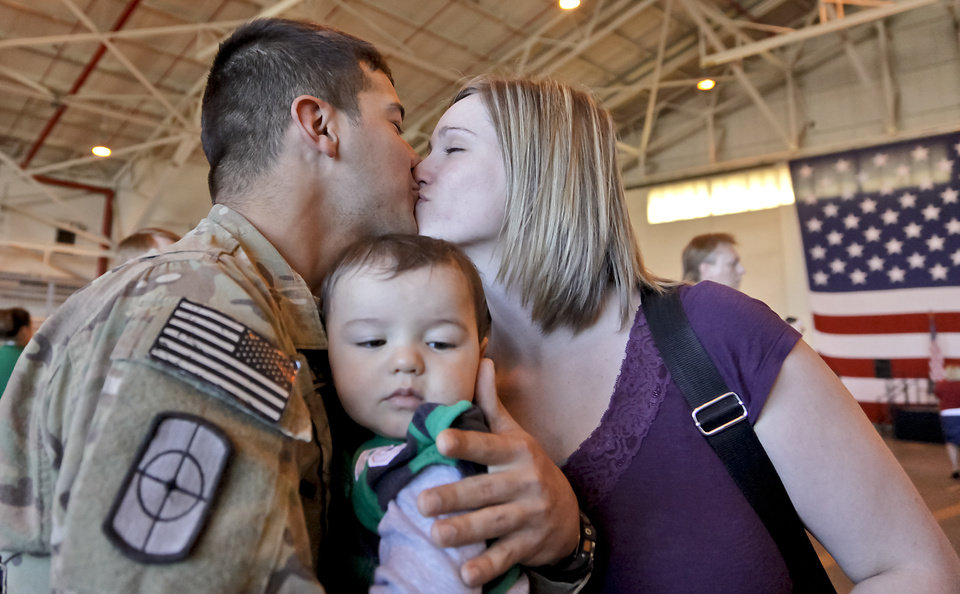 George Delisle kisses his wife Kaylin while holding his seven-month-old son Noah for the first time during the return ceremony for more than 200 National Guard 45th Infantry Brigade Combat Team troops at the National Guard Base on Monday, March 12, 2012, in Oklahoma City, Oklahoma.  Photo by Chris Landsberger, The Oklahoman
