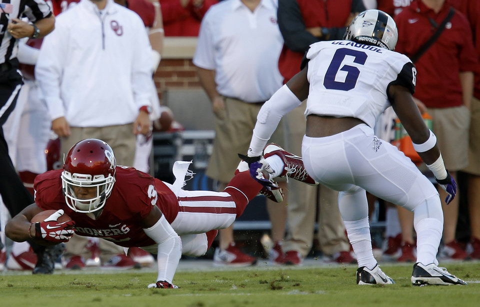 Photo - Oklahoma's Sterling Shepard (3) leaps for yards beside TCU's Elisha Olabode (6) during a college football game between the University of Oklahoma Sooners (OU) and the TCU Horned Frogs at Gaylord Family-Oklahoma Memorial Stadium in Norman, Okla., on Saturday, Oct. 5, 2013. Photo by Bryan Terry, The Oklahoman