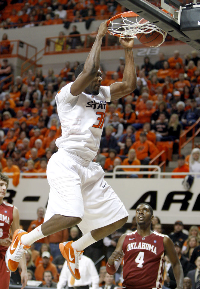 Photo - Oklahoma State's Matt Pilgrim (31) dunks in front of Oklahoma's Andrew Fitzgerald (4) during the Bedlam men's college basketball game between the University of Oklahoma Sooners and Oklahoma State University Cowboys at Gallagher-Iba Arena in Stillwater, Okla., Saturday, February, 5, 2011. Photo by Sarah Phipps, The Oklahoman