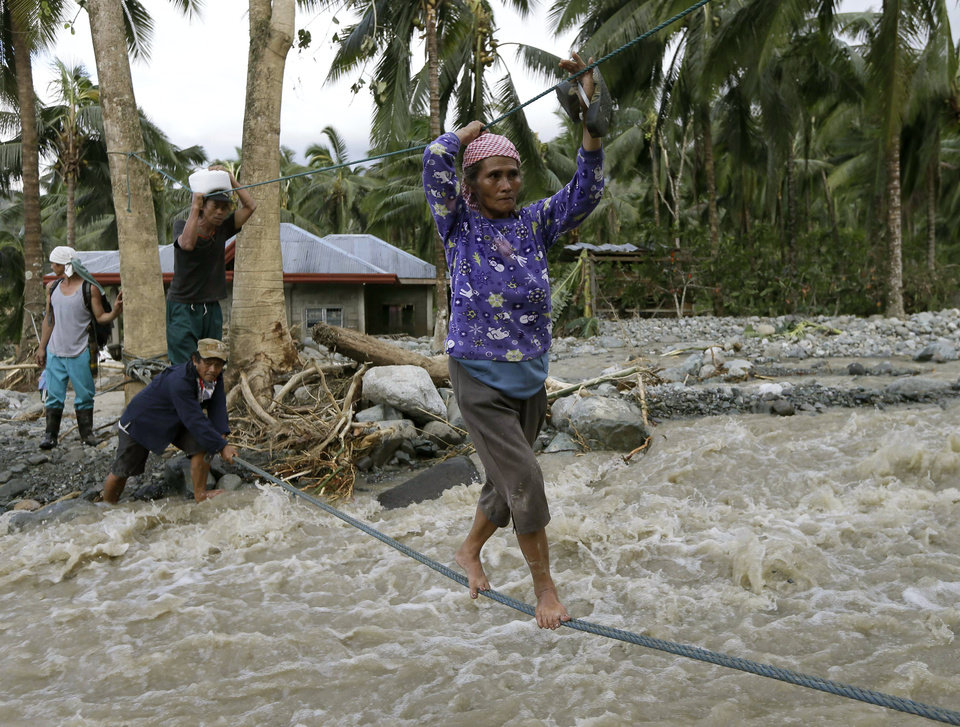 Residents cross a river using suspended ropes at Andap, New Bataan township, Compostela Valley in southern Philippines Wednesday, Dec. 5, 2012, a day after Typhoon Bopha made landfall. Typhoon Bopha, one of the strongest typhoons to hit the Philippines this year, barreled across the country's south on Tuesday, killing scores of people while triggering landslides, flooding and cutting off power in two entire provinces. (AP Photo/Bullit Marquez)