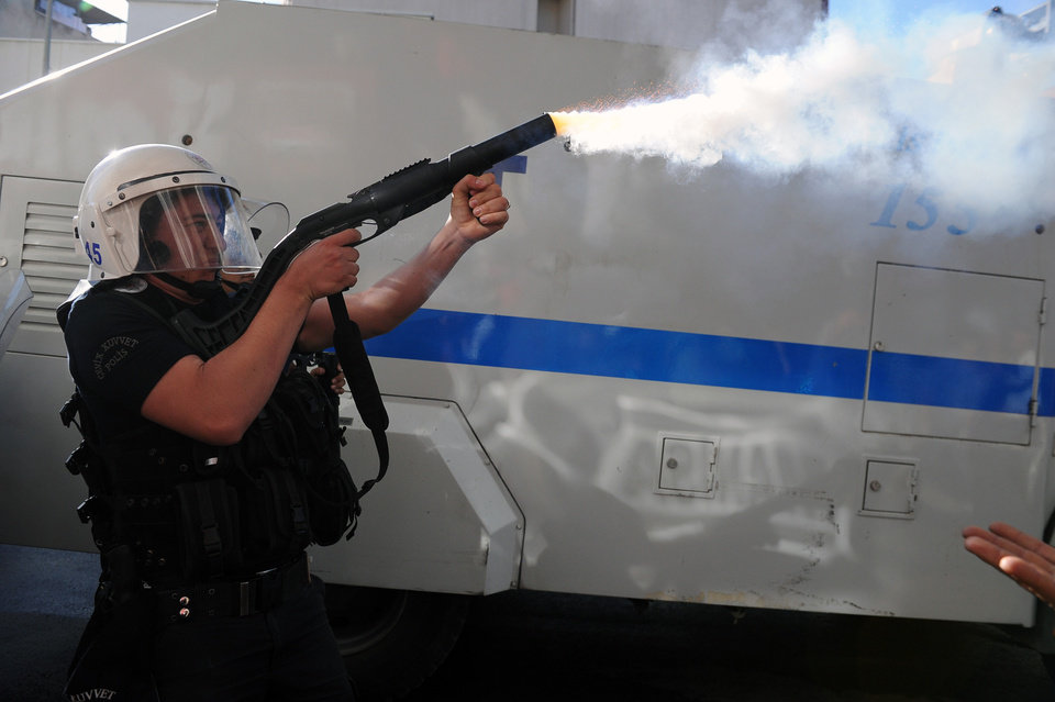 Photo - Riot police officer fires toward demonstrators who are protesting against the government in Soma, Turkey, Friday, May 16, 2014. A Turkish mining company defended its safety record Friday, four days after over 250 people died in an underground blaze at its coal mine in western Turkey.(AP Photo/Emre Tazegul)