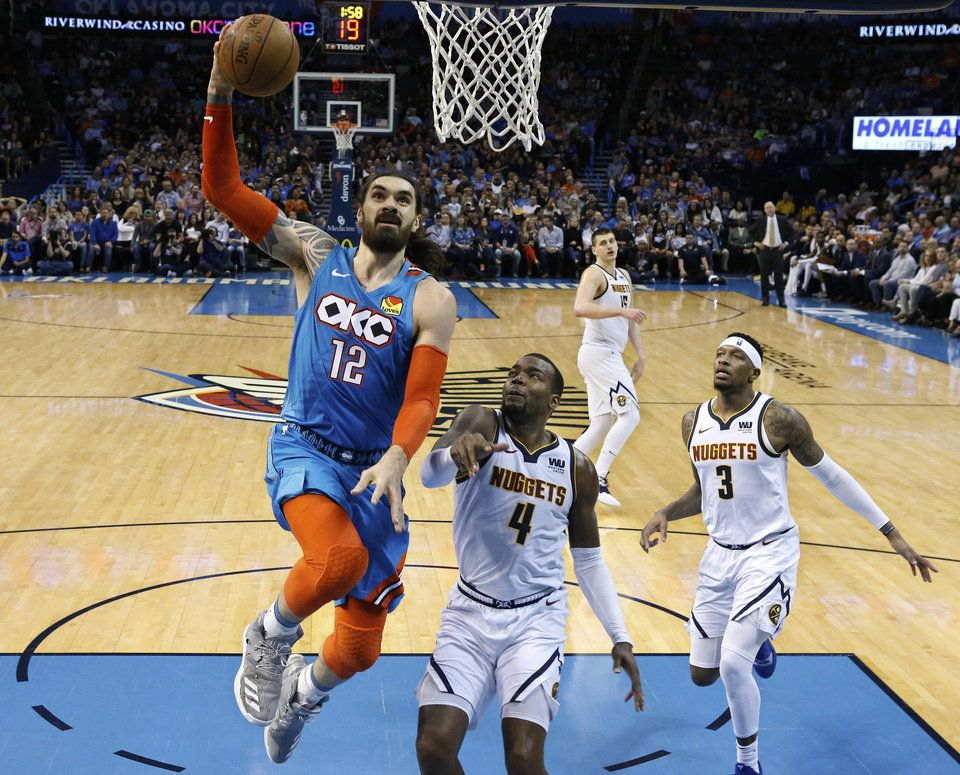 Photo - Oklahoma City Thunder center Steven Adams (12) goes to the basket in front of Denver Nuggets forward Paul Millsap (4) and Torrey Craig (3) during the first half of an NBA basketball game Friday, March 29, 2019, in Oklahoma City. (AP Photo/Sue Ogrocki)
