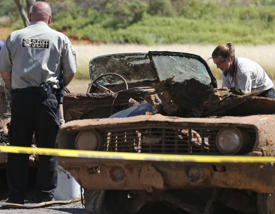Photo - Officials work on the second of two cars found in Foss Lake in Foss, Okla., Wednesday, Sept. 18, 2013. The Oklahoma State Medical ExaminerÂ's Office says authorities have recovered skeletal remains of multiple bodies in the Oklahoma lake where the cars were recovered. (AP Photo/Sue Ogrocki) ORG XMIT: OKSO107