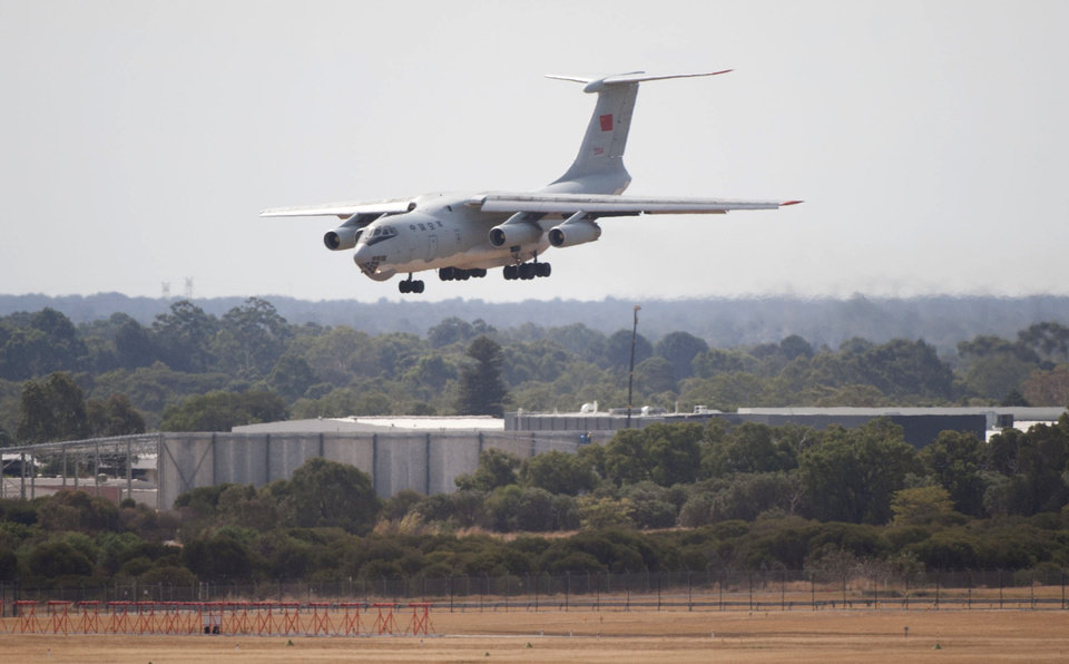 Photo - In this photo released by China's Xinhua news agency, a Chinese IL-76 plane searching for the missing Malaysia Airlines Flight MH370 returns to Perth airport, Australia after a hunting sortie, Monday, March 24, 2014. A Chinese plane on Monday spotted two white, square-shaped objects in an area identified by satellite imagery as containing possible debris from the missing Malaysian airliner, while the United States separately prepared to send a specialized device that can locate black boxes. The crew aboard an IL-76 plane sighted the object in the southern Indian Ocean and reported the coordinates to the Australian command center, which is coordinating the multinational search, as well as the Chinese icebreaker Snow Dragon, which is en route to the area, China's Xinhua News Agency reported. (AP Photo/Xinhua, Lui Siu Wai) NO SALES
