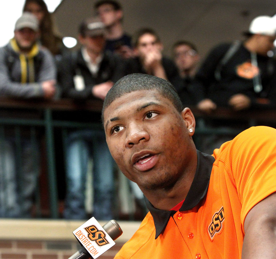 With students crowded on an upper level of the student union to hear the announcement, freshman basketball player Marcus Smart tells fans he has decided to return next year as a student and a member of the Cowboys basketball team. OSU basketball players Le'Bryan Nash, Markel Brown and Marcus Smart delighted  fans when they announced at a noontime press conference they intend to return for another season as members of the Cowboys basketball team. Cheering fans lined all levels in the Student Union atrium Wednesday, April 17, 2013.    by Jim Beckel, The Oklahoman.