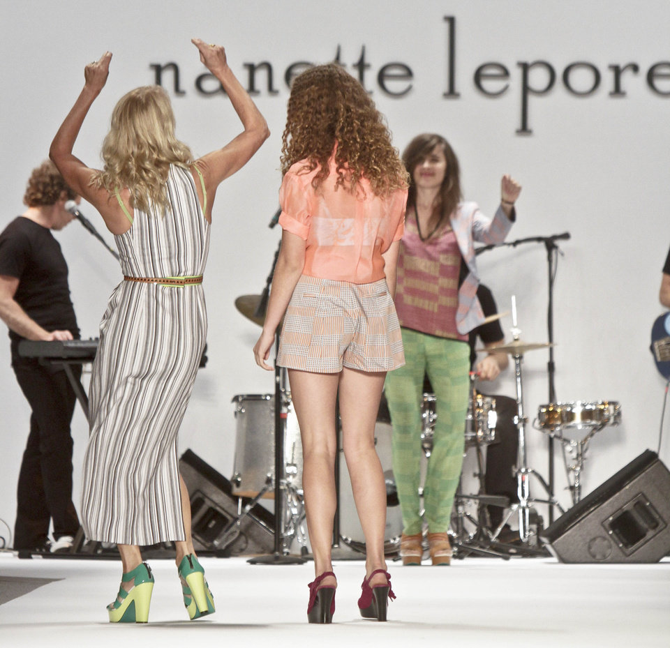 Photo -   Fashion designer Nanette Lepore, left, dances to the live music of the Brazilian Girls band, as she leaves the runway with her daughter Violet, second from right, after unveiling her Spring 2013 collection on Wednesday, Sept. 12, 2012 in New York. (AP Photo/Bebeto Matthews)