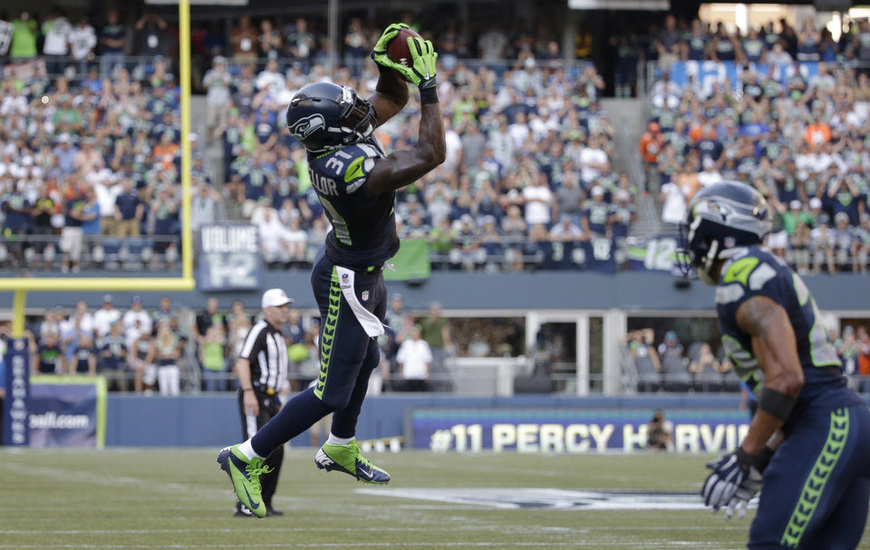 Photo - Seattle Seahawks strong safety Kam Chancellor pulls down an interception in the second half of an NFL football game against the Denver Broncos, Sunday, Sept. 21, 2014, in Seattle. (AP Photo/Elaine Thompson)