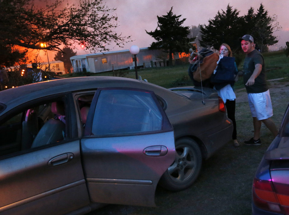 Photo - Residents pack belongings into a car before evacuating a mobile home park near Prairie Grove Rd. and Douglas during wildfires in south Logan County, Sunday, May 4, 2014. Photo by Nate Billings, The Oklahoman