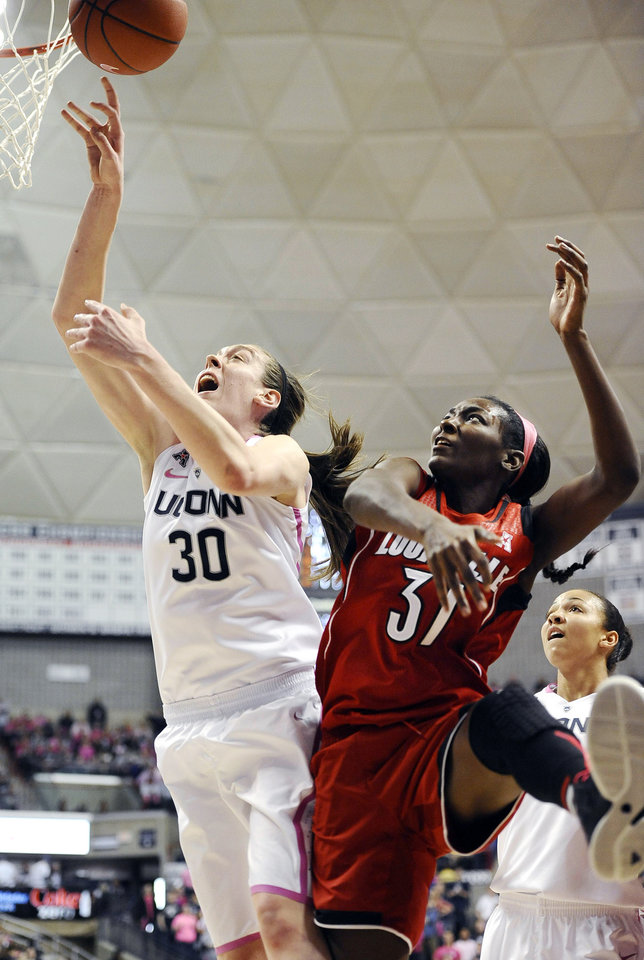 Photo - Connecticut's Breanna Stewart, left, and Louisville's Asia Taylor, battle for a rebound during the second half of an NCAA women's college basketball game, Sunday, Feb. 9, 2014, in Storrs, Conn. Connecticut won 81-64. (AP Photo/Jessica Hill)
