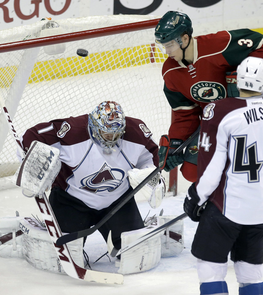 Photo - Minnesota Wild's Charlie Coyle (3) looks for the rebound as Colorado Avalanche goalie Semyon Varlamov, of Russia, defects a shot into the air in the first period of an NHL hockey game, Saturday, Jan. 11, 2014, in St. Paul, Minn. (AP Photo/Jim Mone)