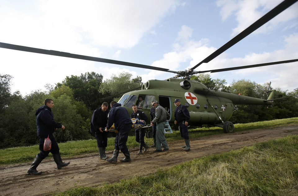 Photo - Serbian police officers carry an old woman from a military helicopter during evacuation from Obrenovac, some 30 kilometers (18 miles) southwest of Belgrade Serbia, Saturday, May 17, 2014. Record flooding in the Balkans leaves at least 20 people dead in Serbia and Bosnia and is forcing tens of thousands to flee their homes. Meteorologists say the flooding is the worst since records began 120 years ago. (AP Photo/Darko Vojinovic)