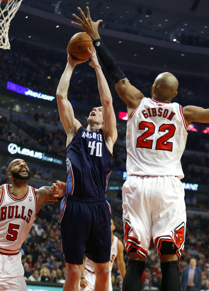 Photo - Charlotte Bobcats center Cody Zeller, center, shoots against Chicago Bulls forward Carlos Boozer, left, and forward Taj Gibson, right, during the first half of an NBA basketball game in Chicago, Saturday, Jan. 11, 2014. (AP Photo/Kamil Krzaczynski)