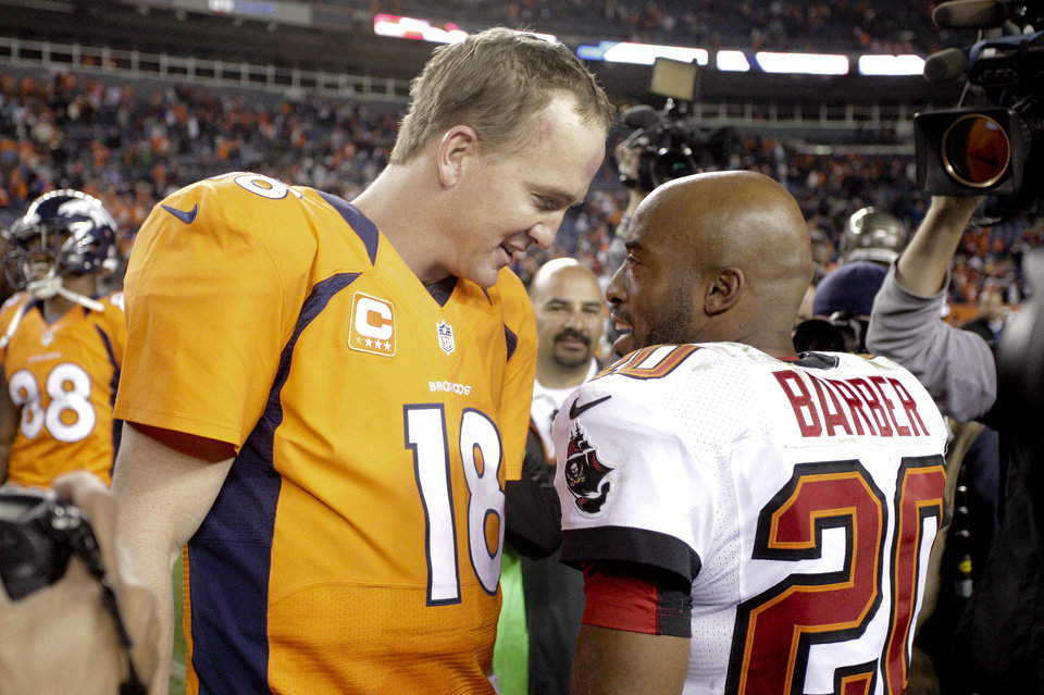 Photo - Denver Broncos quarterback Peyton Manning (18) talks with Tampa Bay Buccaneers free safety Ronde Barber (20) after an NFL football game, Sunday, Dec. 2, 2012, in Denver. Manning passed Pro Football Hall of Famer Dan Marino for the second most completions all-time during the game. Denver won 31-23 and clinched the AFC West division.  (AP Photo/Joe Mahoney)
