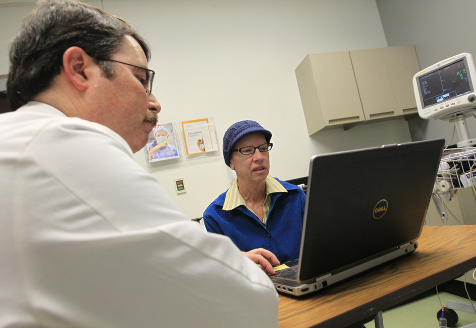 Dr. Doug Scharre, left, administers neurological cognitive tests to Kathleen Sanford Monday, Dec. 17, 2012, in Columbus, Ohio. Sanford is an Alzheimer's patient that has a deep brain stimulation implant as part of a study at Ohio State University. In small experiments, scientists are implanting pacemaker-like devices deep in the brains of some people with early-stage Alzheimer's in hopes of slowing the disease's damage. The tiny wires send mild jolts of electricity to stimulate the brain.  (AP Photo/Jay LaPrete)