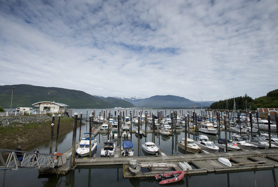 Photo - Boats sit in a harbor in Kitimat, British Columbia, Tuesday, June 17, 2014. Canada's government on Tuesday approved a controversial pipeline proposal that would bring oil to the Pacific Coast for shipment to Asia, a major step in the country's efforts to diversify its oil exports if it can overcome fierce opposition from environmental and aboriginal groups. Approval for Enbridge's Northern Gateway project was expected as Canada needs infrastructure in place to export its growing oil sands production. Enbridge's pipeline would transport 525,000 barrels of oil a day from Alberta's oil sands to the Pacific to deliver oil to Asia, mainly energy-hungry China.  About 220 large oil tankers a year would visit the Pacific coast town of Kitimat. (AP Photo/The Canadian Press, Jonathan Hayward)