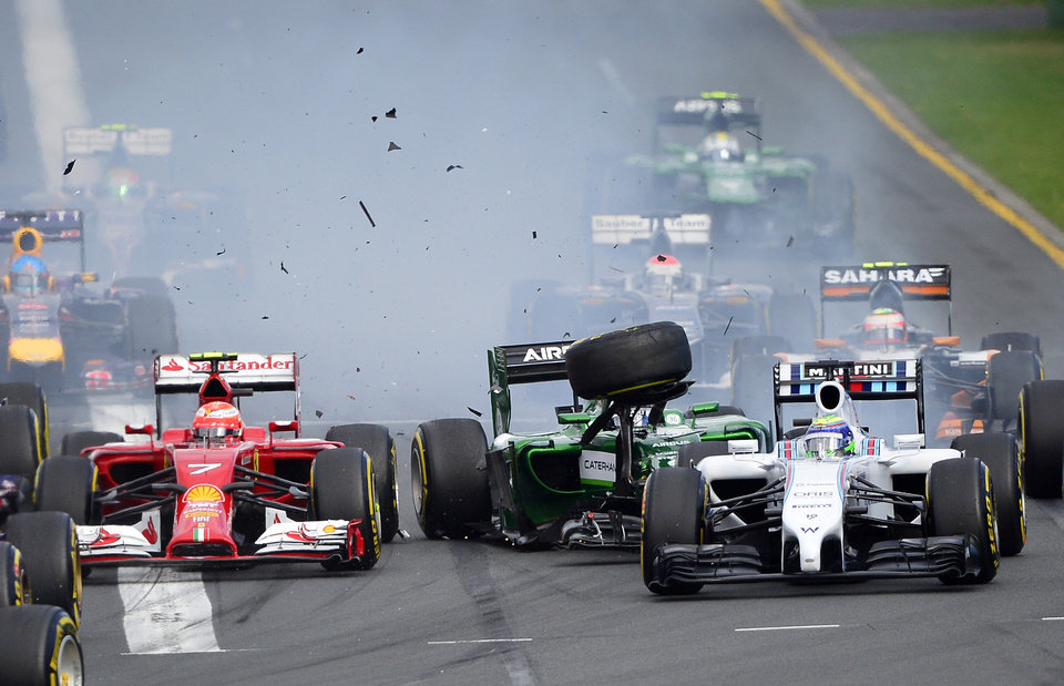 Photo - Williams driver Felipe Massa of Brazil,  right, and Caterham driver Kamui Kobayashi of Japan, center, collide on turn one in  the first lap of the Australian Formula One Grand Prix at Albert Park in Melbourne, Australia, Sunday, March 16, 2014. Both Massa and Kobayashi walked away from the accident. (AP Photo/Ross Land)