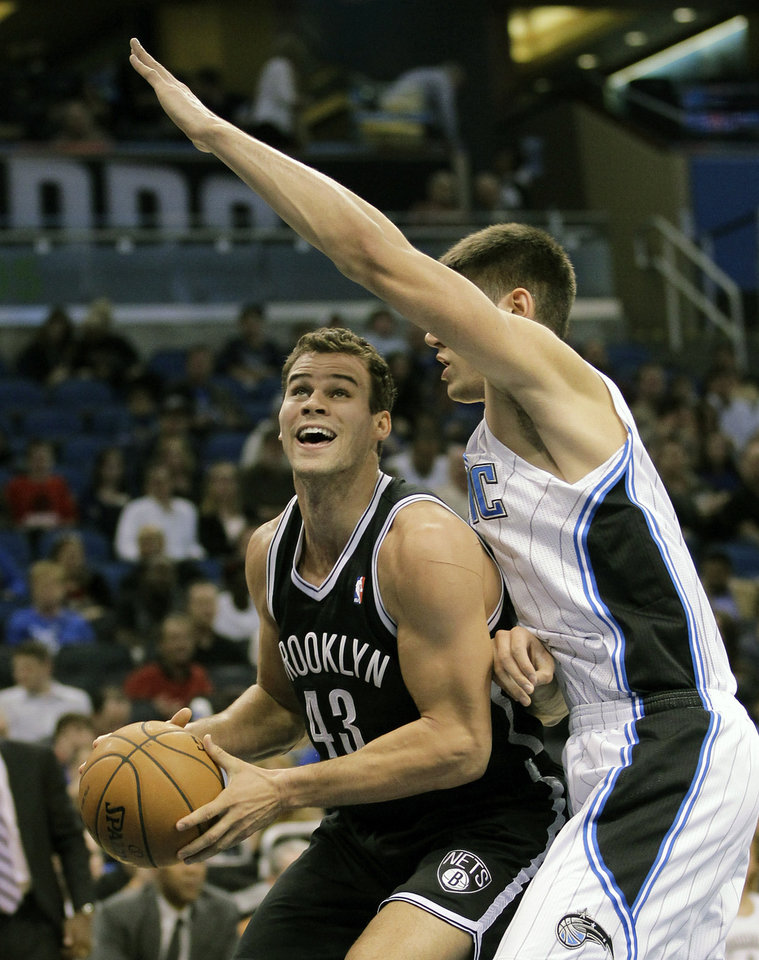 Photo - Brooklyn Nets' Kris Humphries (43) looks for a open shot as he is guarded by Orlando Magic's Nikola Vucevic, of Montenegro, during the first half of an NBA basketball game, Friday Nov. 30, 2012, in Orlando, Fla. (AP Photo/John Raoux)