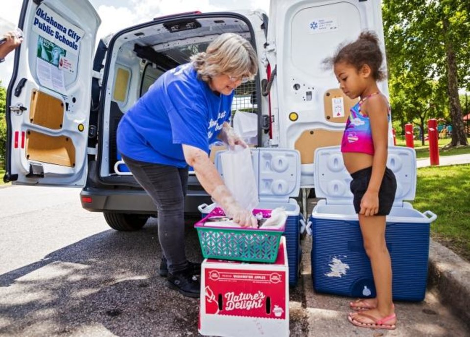 Photo -  Oklahoma City Public School Cafeteria Supervisor Ramona Andruchow helps Mya Jones, 6, pick out items for her lunch during the  Summer Feeding Program from Oklahoma City Public Schools at Wiley Post Park. [Chris Landsberger/The Oklahoman]