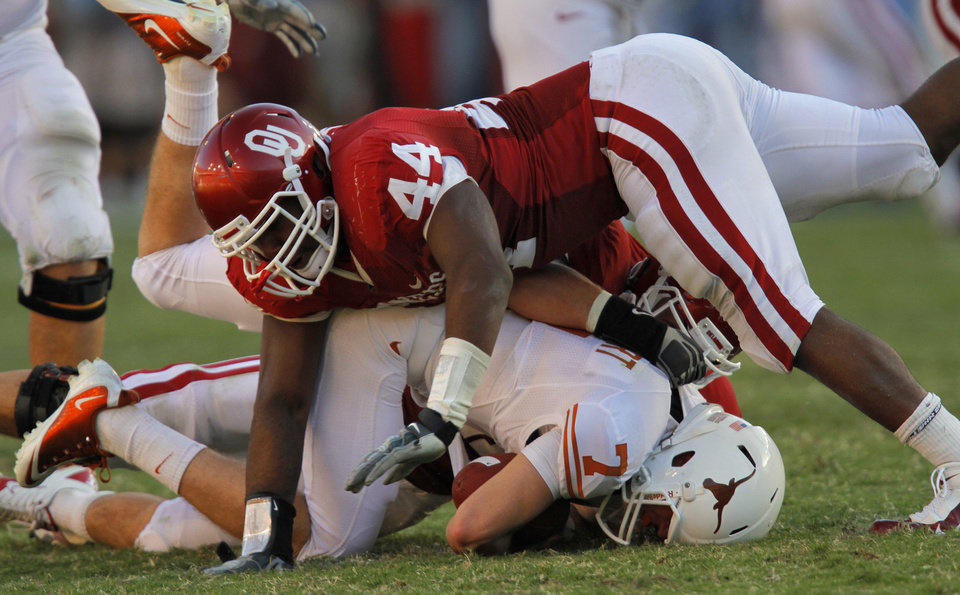 Photo - Oklahoma's Jeremy Beal (44) and Tom Wort (21) sack Texas quarterback Garret Gilbert (7) in the second half of the Red River Rivalry college football game between the University of Oklahoma Sooners (OU) and the University of Texas Longhorns (UT) at the Cotton Bowl on Saturday, Oct. 2, 2010, in Dallas, Texas.   Photo by Chris Landsberger, The Oklahoman
