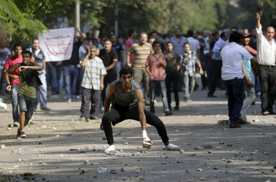 A protester picks up a stone after scuffles broke out between groups of several hundred protesters in Tahrir square when chants against the new Islamist president angered some in the crowd in Cairo, Egypt, Oct. 12, 2012. The scuffles between supporters and opponents of President Mohammed Morsi reflect deep political divisions among the country�s 82 million people, more than a year after the popular uprising that toppled Hosni Mubarak. (AP Photo/Khalil Hamra)