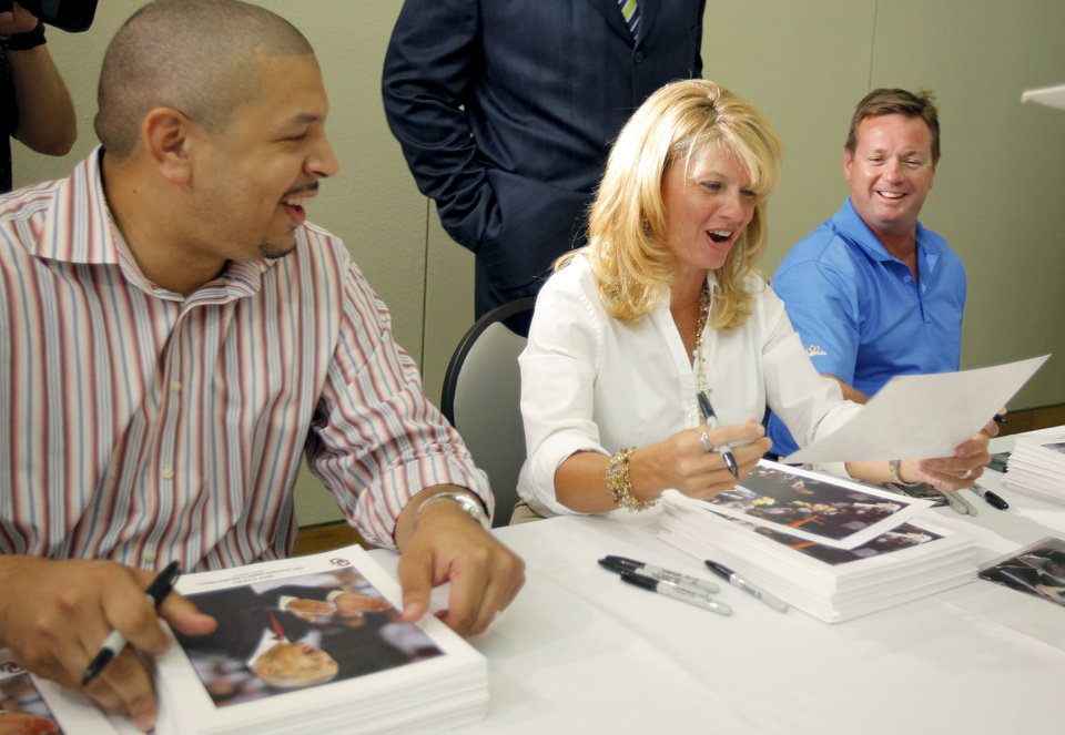 Photo - UNIVERSITY OF OKLAHOMA / COLLEGE FOOTBALL /  WOMEN'S COLLEGE BASKETBALL: OU basketball coach Jeff Capel, left, women's basketball coach Sherri Coale, and football coach Bob Stoops look at a picture during the 2009 Sooner Caravan stop at the National Cowboy & Western Heritage Museum in Oklahoma City, Thursday, August 6, 2009. Photo by Bryan Terry, The Oklahoman ORG XMIT: KOD