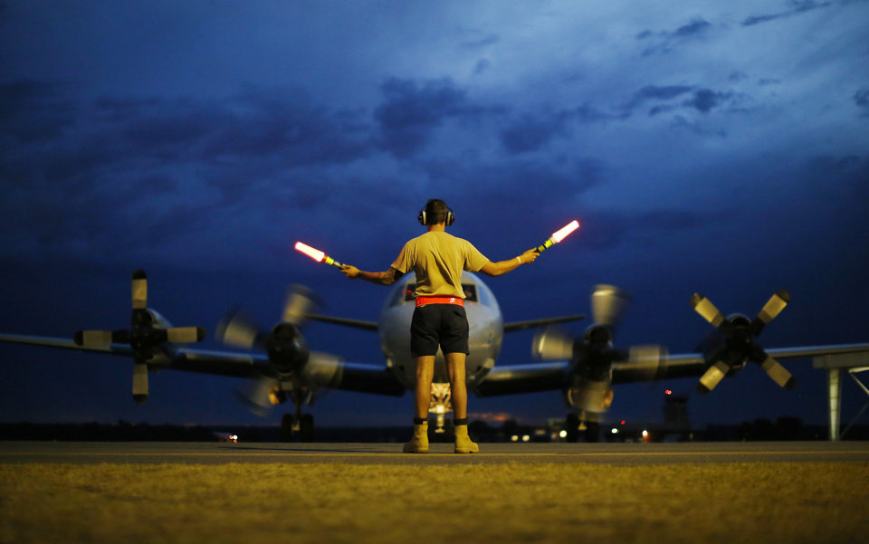 Photo - FILE - In this Monday, March 24, 2014, file photo, a ground controller guides a Royal Australian Air Force AP-3C Orion to rest after sunset upon its return from a search for the missing Malaysia Airlines Flight 370, over the Indian Ocean, at the Royal Australian Air Force Base Pearce in Perth, Australia. The disappearance of Malaysia Airlines Flight 370 has presented two tales of modern technology. The public has been surprised to learn of the limitations of tracking and communications devices, which contributed to the plane vanishing for more than two weeks. But the advanced capabilities of some technologies, particularly satellites, have provided hope that the mystery won't go unsolved. (AP Photo/Jason Reed, Pool, File)