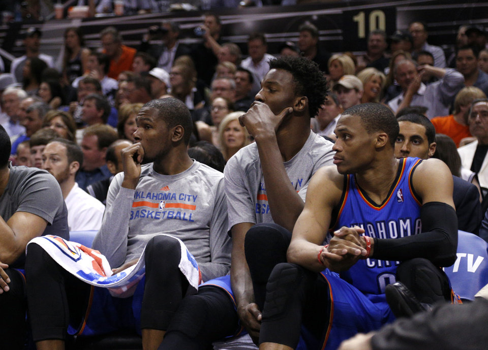 Photo - Oklahoma City's Kevin Durant (35), Hasheem Thabeet (34) and Oklahoma City's Russell Westbrook (0) watch the final minutes during Game 2 of the Western Conference Finals in the NBA playoffs between the Oklahoma City Thunder and the San Antonio Spurs at the AT&T Center in San Antonio, Wednesday, May 21, 2014. Photo by Sarah Phipps