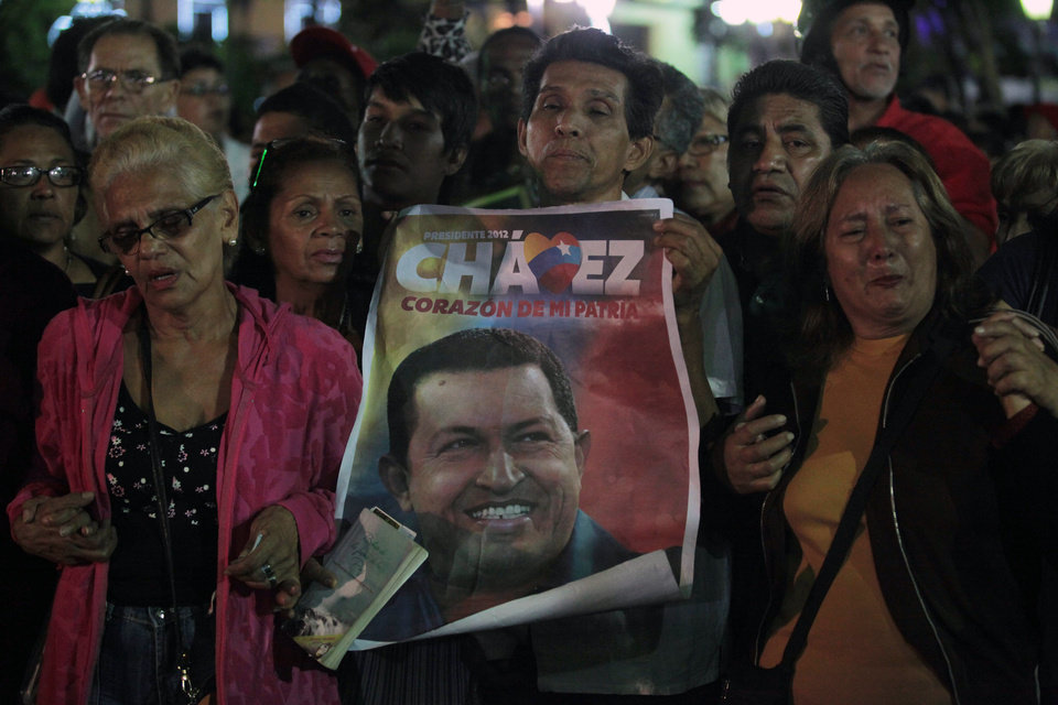 Photo - People, one holding up an image of  Venezuela's President Hugo Chavez gather to pray for him at Simon Bolivar square in Caracas, Venezuela, Tuesday, Dec. 11, 2012. Doctors began operating on Chavez  in Cuba, his government said, after his cancer reappeared despite a year and a half of surgeries and treatments. (AP Photo/Fernando Llano)