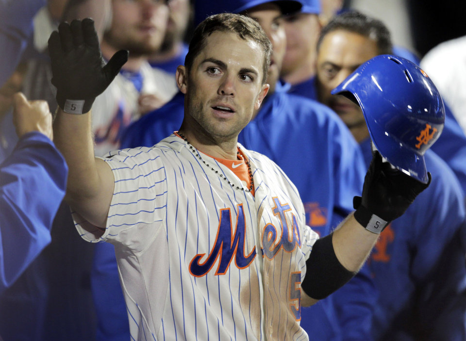 FILE - In this April 25, 2012 file photo, New York Mets\' David Wright is greeted by teammates in the dugout after hitting a two-run home run during the sixth inning of a baseball game against the Miami Marlins in New York. WFAN radio is reporting Friday, Nov. 30, 2012, that Wright and the New York Mets have agreed to a $138 million, eight-year contract that would be the richest in franchise history. (AP Photo/Seth Wenig, File)