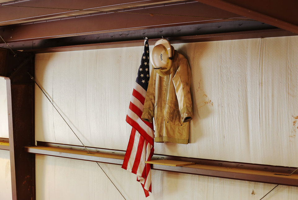 Photo - Above left:  A bunker coat and a chief's helmet hang beside an American flag above the lockers of volunteer firefighters Tuesday inside the fire station.  Photos by Jim Beckel, The Oklahoman  Jim Beckel -  THE OKLAHOMAN