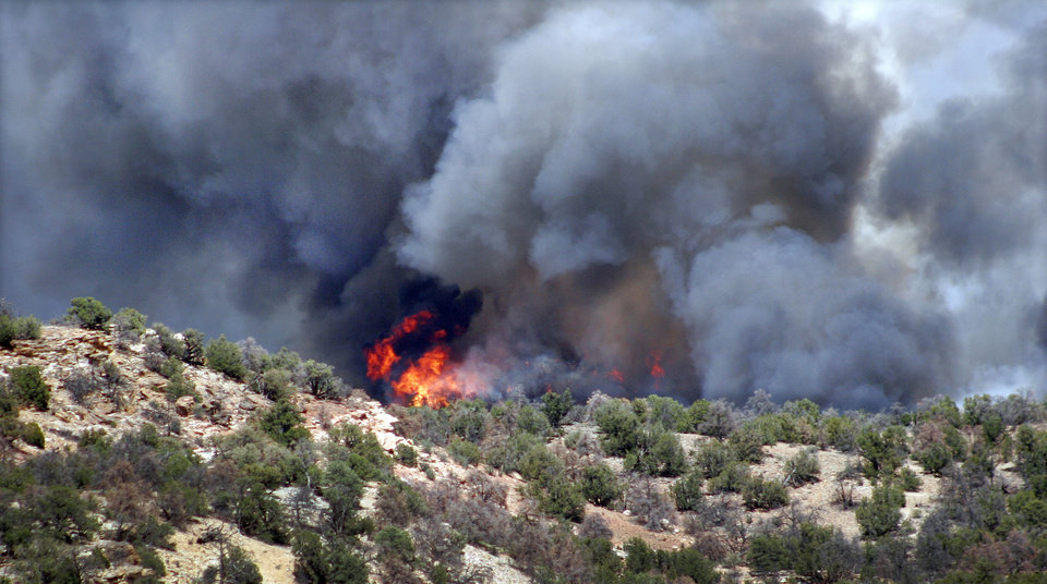 Photo - Black smoke billows above flames near the south rim entrance to the Royal Gorge Bridge at County Road 3 in western Fremont County Tuesday afternoon, June 11, 2013 west of Canon City, Colo. The fire was one of several that started across the state in the midst of recording-setting hot temperatures and high winds. (AP Photo/The Pueblo Chieftain, Tracy Harmon)