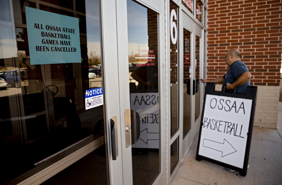 Photo - Yukon High School's John Paul Esparza takes down parking signs as he goes through the doors where signs hang on the door at Yukon High School announcing the cancelation of the Oklahoma Secondary School Activities Association state basketball playoff games at the school in Yukon, Okla. on Thursday, March 12, 2020.   [Chris Landsberger/The Oklahoman]