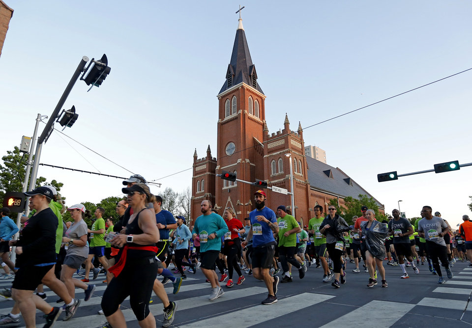 Photo - Runners move south on Harvey during the Oklahoma City Memorial Marathon in Oklahoma City, Sunday, April 28, 2019. [Bryan Terry/The Oklahoman]