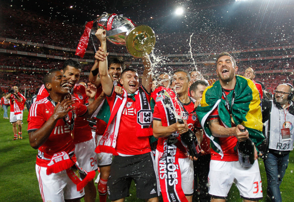 Photo - Benfica's Guilherme Siqueira lifts the trophy as teammates Lima and Jardel, right, spray sparkling wine celebrating at the end of their Portuguese league soccer match with Olhanense Sunday, April 20 2014, at Benfica's Luz stadium in Lisbon. Benfica defeated Olhanense 2-0 to win the championship with two rounds left to play. (AP Photo/Francisco Seco)