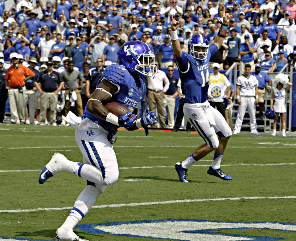 Photo - Kentucky running back Jojo Kemp (3) scores against Tennessee-Martin on a run as quarterback Patrick Towles (14) celebrates in the background during an NCAA college football game in Lexington, Ky., Saturday, Aug. 30, 2014. (AP Photo/Garry Jones)