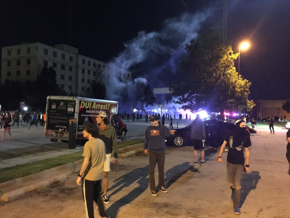 Photo - Protesters scatter as Oklahoma City Police fire tear gas into the crowd near police headquarters Sunday, May 31, 2020, in Oklahoma City. Photo by Chris Casteel