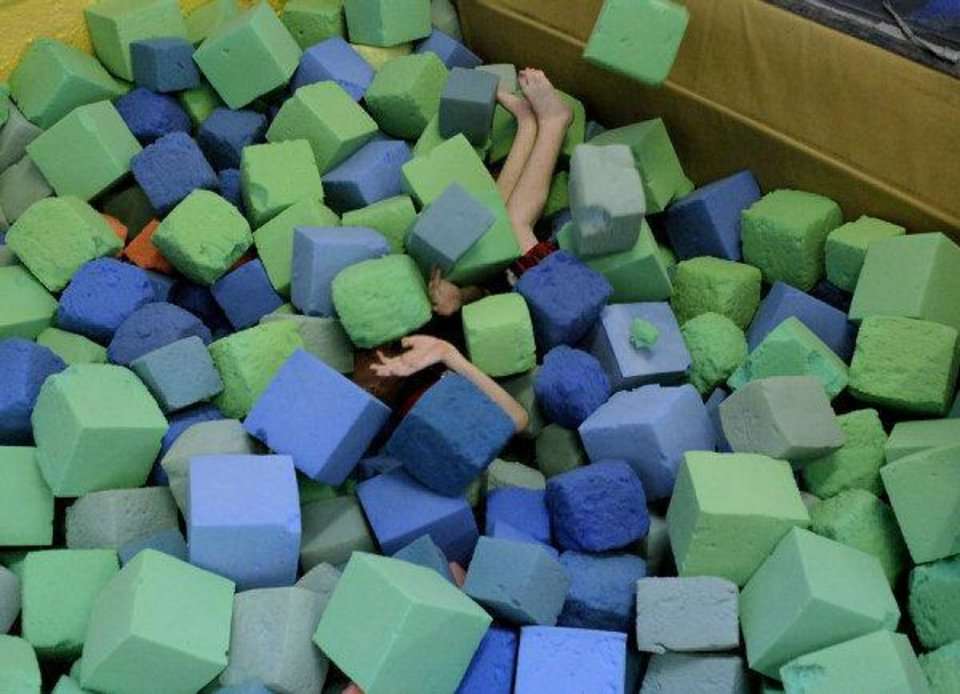 Kane Barton, of Oklahoma City, is covered in foam cubes as he falls into a pit at Mat Trotters Gymnastics in Oklahoma City on Wednesday at the Oklahomans Without Limits summer camp for blind or visually impaired children. PHOTO BY JOHN CLANTON, THE OKLAHOMAN <strong>JOHN CLANTON - John Clanton</strong>