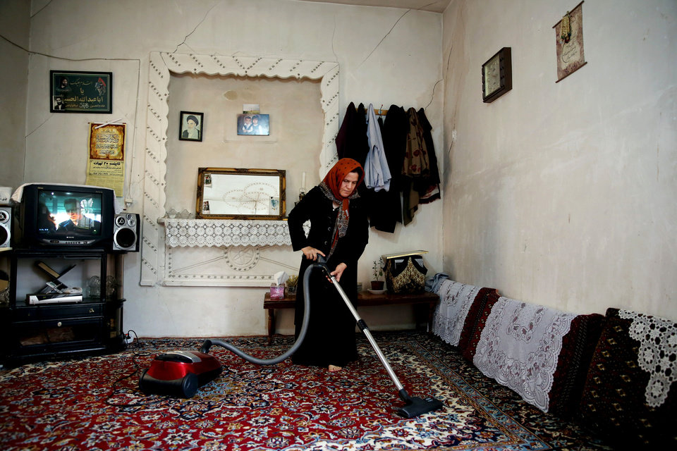 Photo - In this June, 22, 2014 photo, Mehri, uses a solar-powered vacuum cleaner on a carpet at her home in Sichanloo, a hamlet 200 kilometers (125 miles) northwest of the capital, Tehran, Iran. President Hassan Rouhani's administration, sees a bright future in solar, spending $60 million this year on solar projects compared to just $12 million to last year. They especially want to target rural communities largely cut off from government services across the country. In Sichanloo, the seven families who live here once relied on gasoline-fueled generators for electricity. (AP Photo/Ebrahim Noroozi)