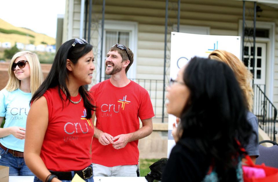 Photo -       Nate Tunnell, minister and director of Cru, center, and Stephanie Knight, left, greet incoming students at the University of Utah in Salt Lake City on Friday, Aug. 22, 2014. (Laura Seitz, Deseret News)