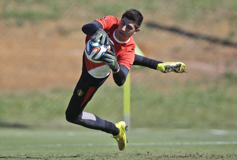 Photo - Belgium's goalkeeper Thibaut Courtois jumps to catch the ball during a team training session in Mogi Das Cruzes, Brazil, Friday, June 13, 2014. Belgium play in group H of the 2014 soccer World Cup. (AP Photo/Andrew Medichini)