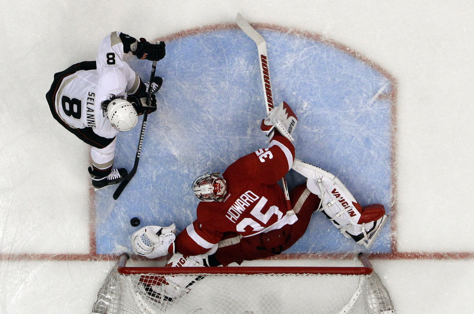 Photo - Detroit Red Wings goalie Jimmy Howard (35) stops a Anaheim Ducks right wing Teemu Selanne (8), of Finland, shot in the second period in Game 6 of a first-round NHL hockey Stanley Cup playoff series in Detroit, Friday, May 10, 2013. Detroit won 4-3 in overtime. (AP Photo/Paul Sancya)