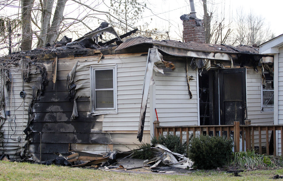 Photo - This Sunday, March 10, 2013 photo shows the charred remains of a home after a fire erupted, Saturday, March 9, 2013 in Gray, Ky, killing two adults and five children inside. (AP Photo/Lisa Norman-Hudson)