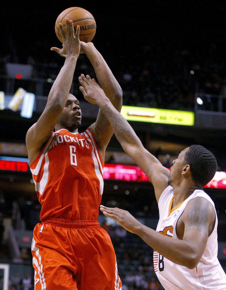 Photo - Houston Rockets power forward Terrence Jones (6) shoots over Phoenix Suns power forward Channing Frye (8) in the first quarter of an NBA basketball game, Sunday, Feb. 23, 2014, in Phoenix. (AP Photo/Rick Scuteri)