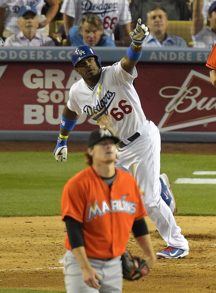 Photo - Los Angeles Dodgers right fielder Yasiel Puig, top, hits a three-run home run as Miami Marlins starting pitcher Tom Koehler stands on the field during the fourth inning of a baseball game, Monday, May 12, 2014, in Los Angeles. (AP Photo)