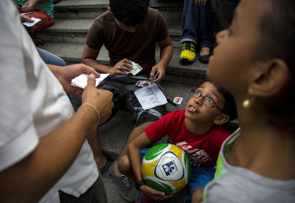Photo - People exchange stickers of soccer players to complete their World Cup sticker albums at a meeting of collectors in Caracas, Venezuela, Saturday, June 21, 2014. Traders say the hobby provides a connection to the tournament, and a distraction from the troubles that have recently wracked the country. (AP Photo/Ramon Espinosa)