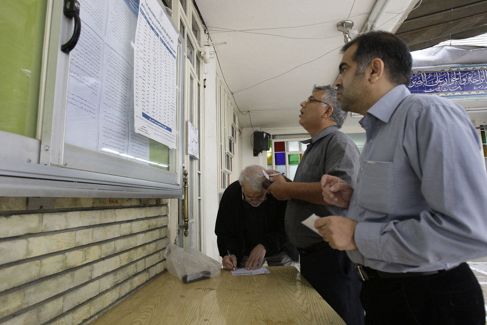 Photo -   Iranian voters check the list of the candidates and fill in the ballots in the parliamentary runoff elections at a polling station in Tehran, Iran, Friday, May 4, 2012. The country has begun runoff elections for more than one-fifth of parliamentary seats. Friday's report says 130 hopefuls will compete for 65 seats in 33 constituencies including the capital Tehran with 25 undecided seats. (AP Photo/Vahid Salemi)