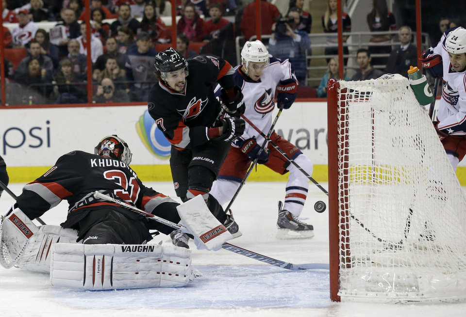 Photo - Columbus Blue Jacket's Derek MacKenzie (24), far right, scores against Carolina Hurricanes goalie Anton Khudobin (31) as Hurricanes' Justin Faulk (27) and Blue Jackets' Corey Tropp (26) look on during the first period of an NHL hockey game in Raleigh, N.C., Monday, Jan. 27, 2014. (AP Photo/Gerry Broome)