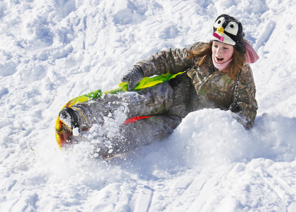 Photo - Zoe Hungate, 11, falls off her sleds in a park in Fairfield addition in Edmond, Wednesday, February 2, 2011.        Photo by David McDaniel, The Oklahoman