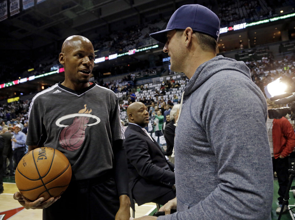 Miami Heat\'s Ray Allen, left, talks to Green Bay Packers quarterback Aaron Rodgers before the first half of Game 3 in their first-round NBA basketball playoff series against the Milwaukee Bucks, Thursday, April 25, 2013, in Milwaukee. (AP Photo/Morry Gash)